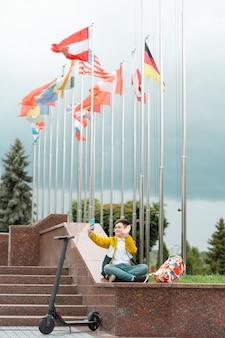 O adolescente senta-se perto do edifício da administração no contexto das bandeiras do país e acena para o smartphone.