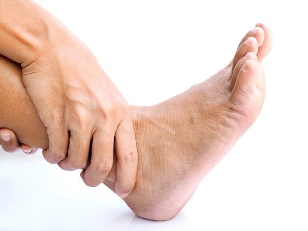 O adulto asiático com dor no tornozelo da inflamação do ligamento e do músculo, usa as mãos para massagear na perna ou nos pés doloridos, isolados na superfície branca.
