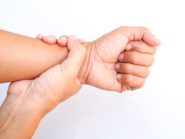 O adulto asiático que sofre da dor no pulso, usa o toque da mão no braço e faz massagens no pulso para aliviar, parte do corpo isolada na superfície branca.
