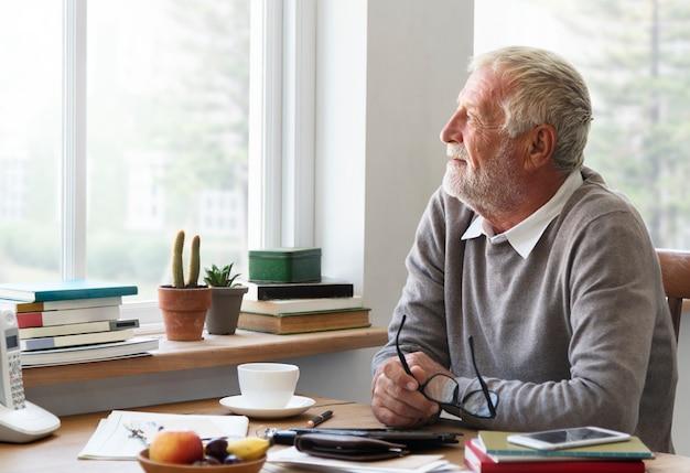 O adulto sênior que olha a janela exterior relaxa o conceito
