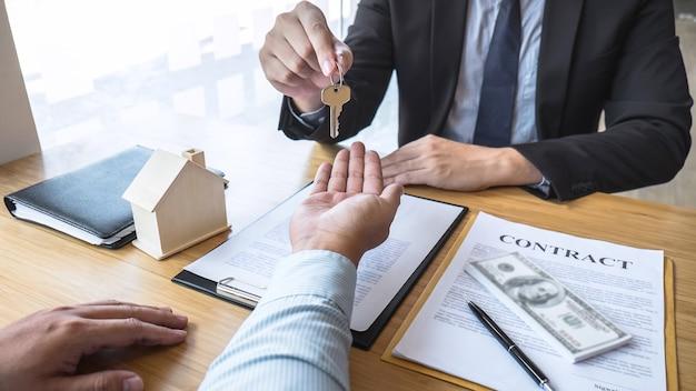 O agente imobiliário está apresentando o empréstimo à habitação e enviando as chaves ao cliente após a assinatura do contrato de compra da casa com o formulário de pedido de propriedade aprovado, conceito insurance home.