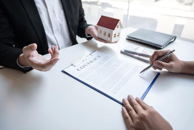 O agente imobiliário está apresentando o empréstimo à habitação e enviando as chaves ao cliente após a assinatura do contrato