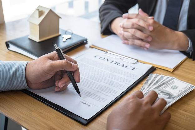 O agente imobiliário está apresentando o empréstimo e dando as chaves da casa ao cliente após a assinatura do contrato