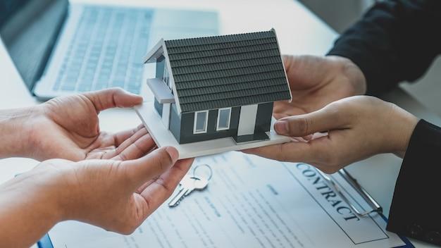 O agente imobiliário segura o modelo da casa e explica o contrato de negócios para a mulher compradora