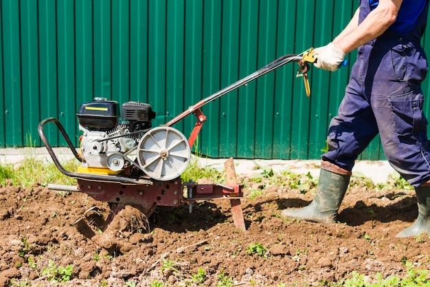 O agricultor ara a terra com um cultivador. trabalhadores agrícolas com tratores. cultivador a motor para preparo do solo no jardim. plantando vegetais.