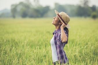O agricultor está no campo de arroz e cuida do seu arroz.