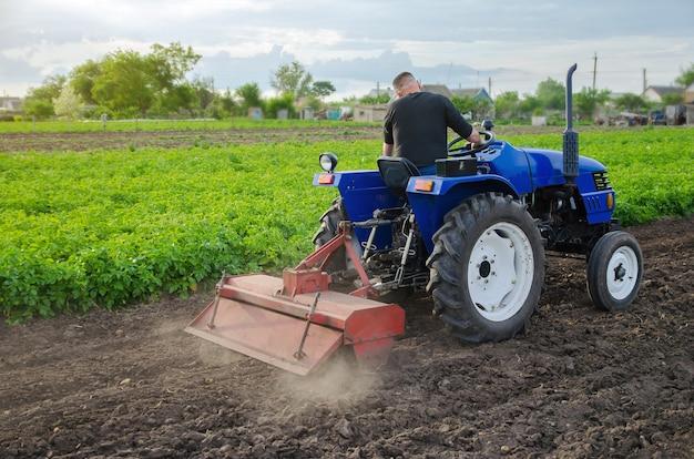 O agricultor solta e cultiva o solo do campo. moagem do solo, trituração antes de cortar as linhas