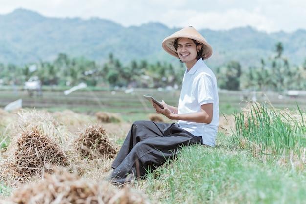 O agricultor sorri de chapéu sentado no campo de arroz usando um tablet digital após a colheita no campo