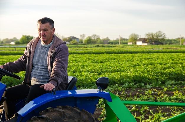 O agricultor trabalha no campo com um trator.