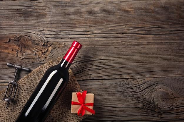 O ajuste do jantar do feriado com vinho tinto e presente na madeira rústica no plano coloca a vista.