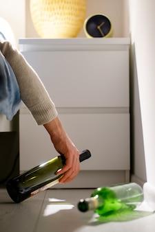 O alcoólatra adormeceu com uma garrafa na mão na cama depois da festa, garrafas de vinho vazias no chão. embriaguez, conceito de ressaca