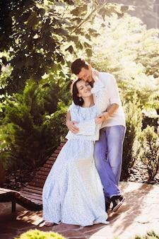 O alegre homem encaracolado se inclina para o concurso de sua senhora enquanto ela o abraça no banco de madeira
