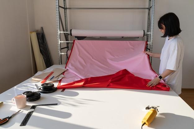 O alfaiate escolhe o material para o trabalho de costureira de coleção de capa de chuva da moda em um estúdio de moda ou oficina