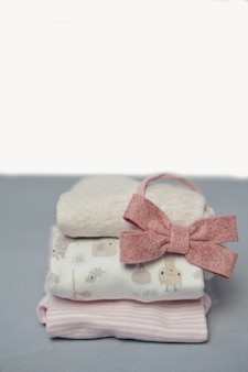 O algodão colorido dobrou a pilha da roupa no fundo vazio do espaço da tabela branca, lavanderia do bebê.