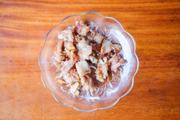 O alho fritou o saque da carne de porco no prato branco ajustado na tabela marrom - conceito caseiro do alimento.
