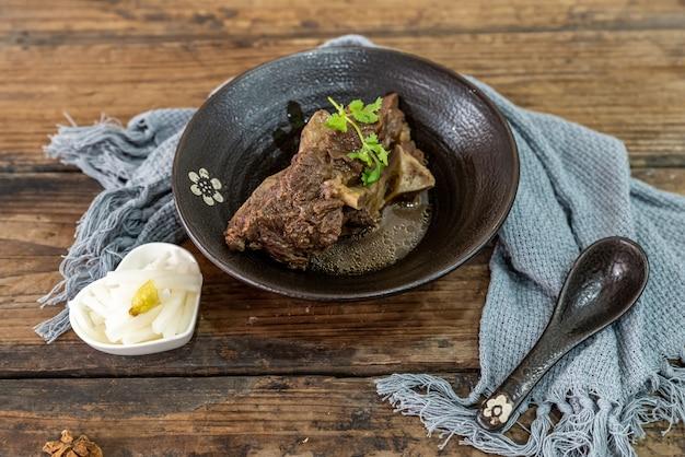 O alimento feito de carne bovina está na tigela sobre a toalha da mesa de madeira