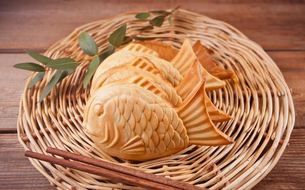 O alimento japonês da rua de taiyaki peixe-deu forma ao waffle de enchimento doce na tabela de madeira.