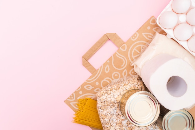 O alimento para o período de isolamento da quarentena liso coloca no espaço amarelo com espaço da cópia. ovos, macarrão, feijão, papel higiênico, maçã e algumas seleções. crise alimentar.