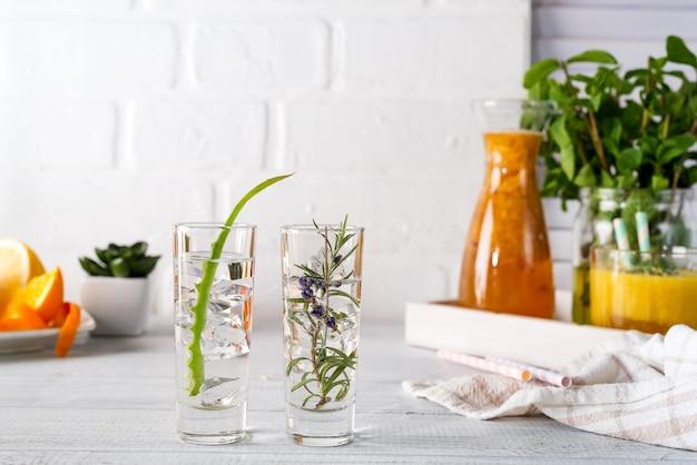 O aloés vera e alecrins gim e tônico na tabela rústica branca.
