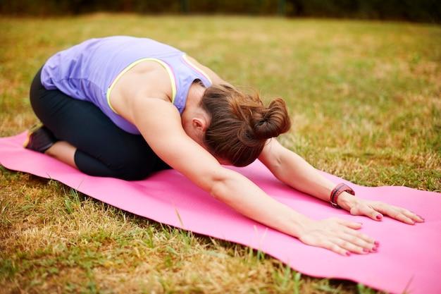 O alongamento é muito importante após os exercícios físicos. jovem mulher fazendo ioga lá fora.