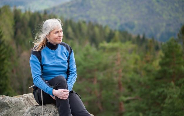 O alpinista fêmea idoso senta-se no pico da rocha