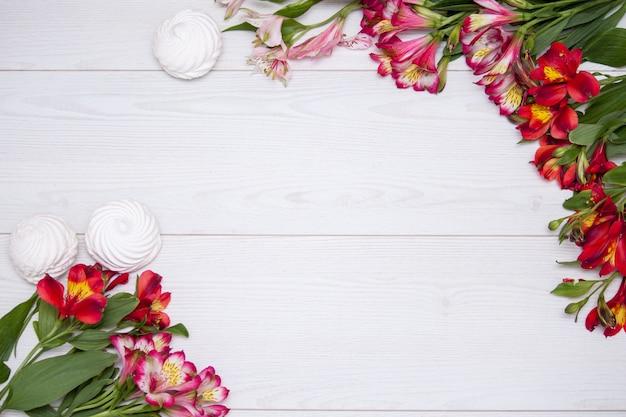 O alstroemeria floresce o fundo com zephir branco no fundo de madeira branco.