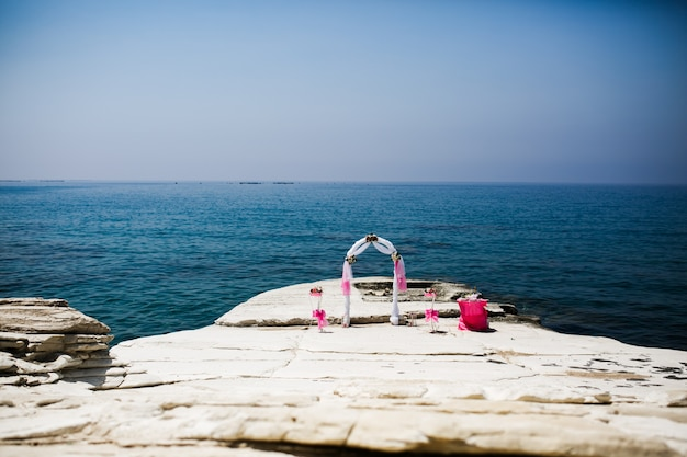 O altar de casamento rosa está de pé nas pedras