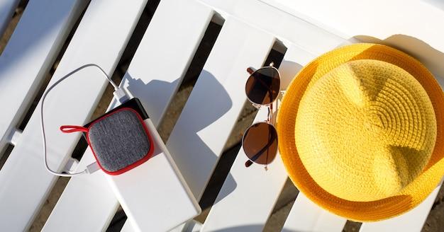 O alto-falante portátil de música é carregado no banco de energia via usb em uma espreguiçadeira perto da piscina com acessórios de praia.