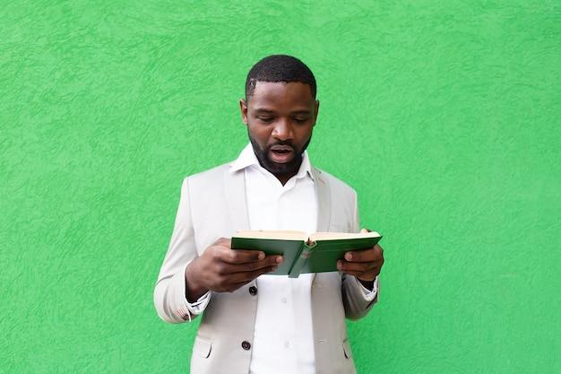 O aluno com um livro em uma parede verde