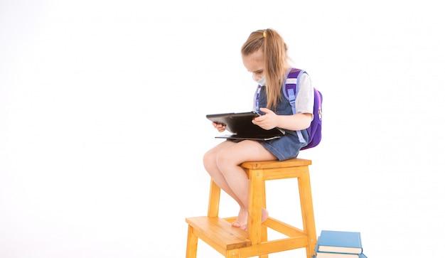 O aluno da primeira série em máscara médica aprende a ler. menina no ensino a distância em casa.