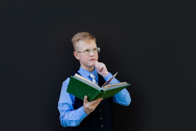 O aluno do menino com um livro sobre um fundo preto