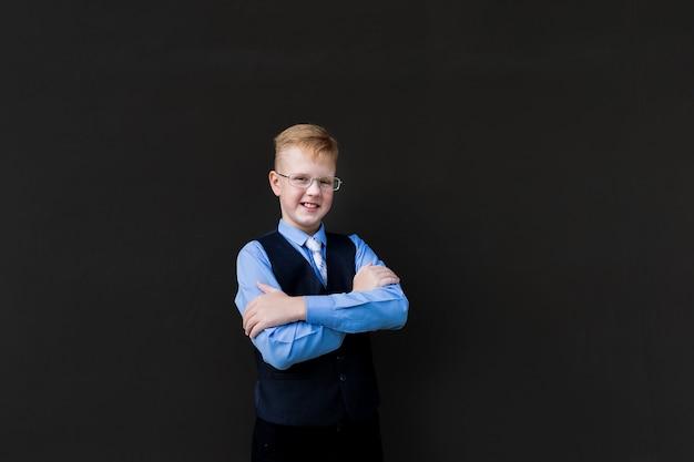 O aluno do menino em um fundo preto