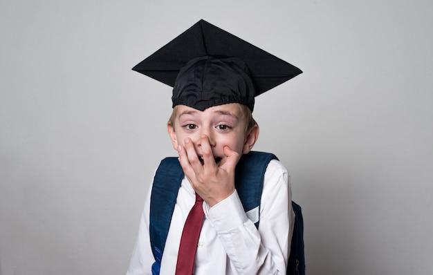 O aluno surpreso cobriu a boca com as mãos. rapaz usando chapéu de pós-graduação. conceito de escola secundária
