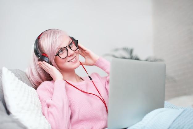 O aluno tem prazer em se comunicar com os amigos via internet. escolaridade em casa, trabalho e estudo, novo conhecimento. adolescente feliz na cama com o computador. estudante deitada na cama sorrindo.