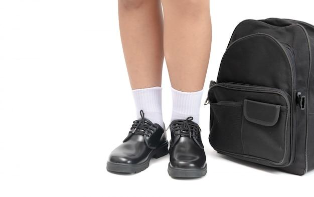 O aluno usa um sapato de couro preto e uma mochila escolar.