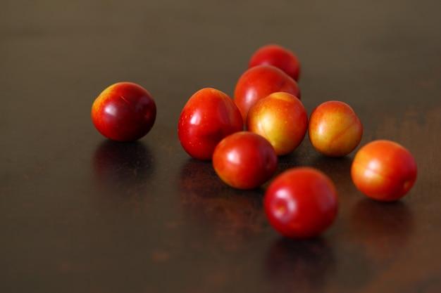 O amarelo vermelho do fruto da ameixa dispersou no tabletop marrom riscado velho de madeira.