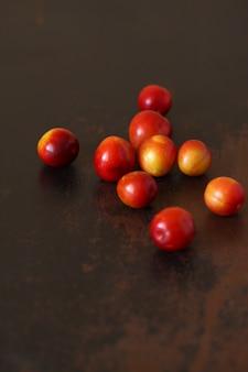 O amarelo vermelho do fruto da ameixa dispersou no tabletop marrom velho de madeira.