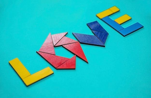 O amor de inscrição. letras coloridas feitas de formas geométricas de madeira. o conceito de dia dos namorados e casamento. Foto Premium