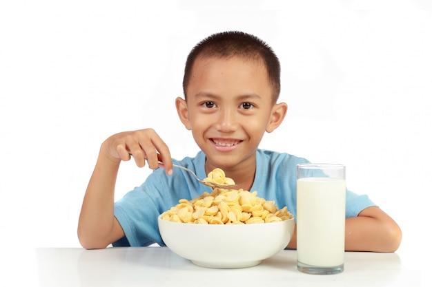O amor do garoto em tomar café da manhã com leite contra fundo branco