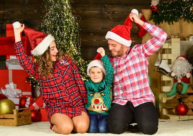 O amor está no ar. família feliz comemorar o natal. filho com os pais no chapéu de papai noel. garotinho menino amo a mãe e o pai. amo passar férias juntos. se divertindo. ano novo em casa. retrato de família de natal.
