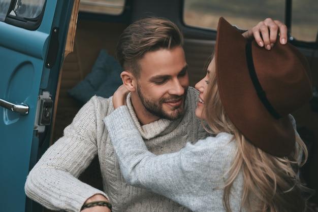 O amor está no ar. lindo casal jovem se abraçando e sorrindo enquanto está sentado em uma mini van azul estilo retro