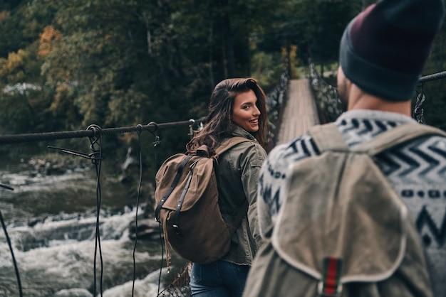 O amor torna tudo possível. lindo casal jovem de mãos dadas e sorrindo enquanto caminha na ponte pênsil