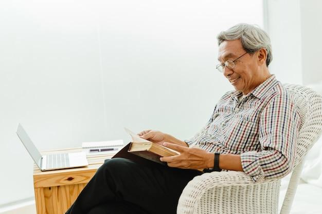 O ancião asiático feliz gosta de ler um livro para aprender durante o covid-19 em casa, em quarentena.