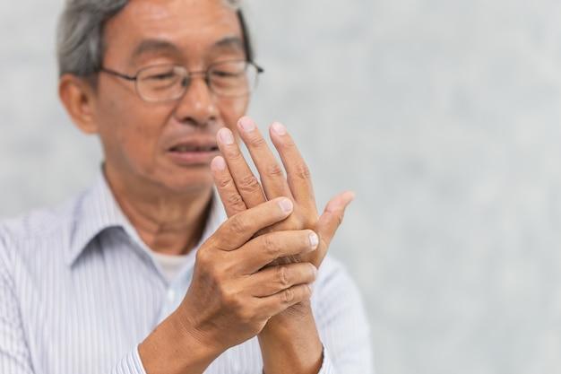 O ancião asiático sofre a dor de músculo do tendão da palma da mão.