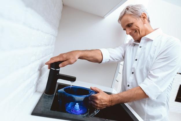 O ancião na camisa derrama a água da torneira na cozinha.