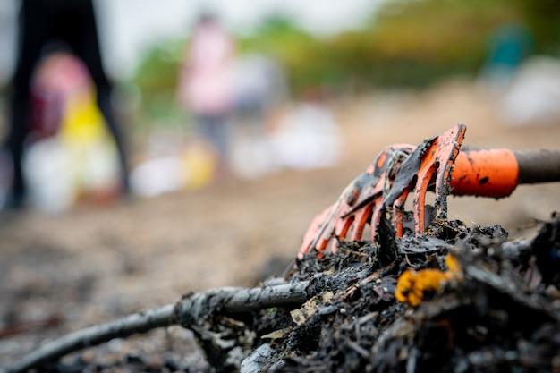 O ancinho alaranjado do close up na pilha de desperdício sujo no fundo borrado do voluntário limpa a praia. conceito da poluição ambiental da praia arrumando desperdícios na praia. lixo do oceano. costa poluída.