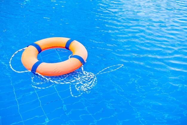 O anel alaranjado da associação do boia salva-vidas flutua na água azul. anel de vida na piscina, anel de vida flutuando em cima de água azul ensolarada