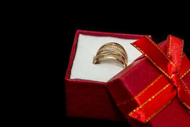O anel dourado em uma pequena caixa vermelha é isolado na superfície preta