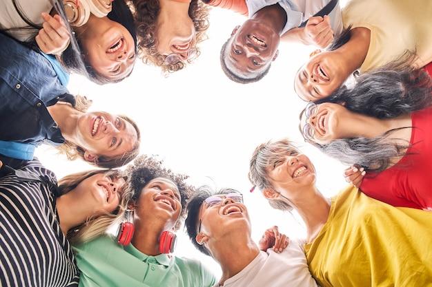 O ângulo baixo de um grupo de alunos está junto com os rostos felizes e sorridentes de jovens adolescentes se abraçando