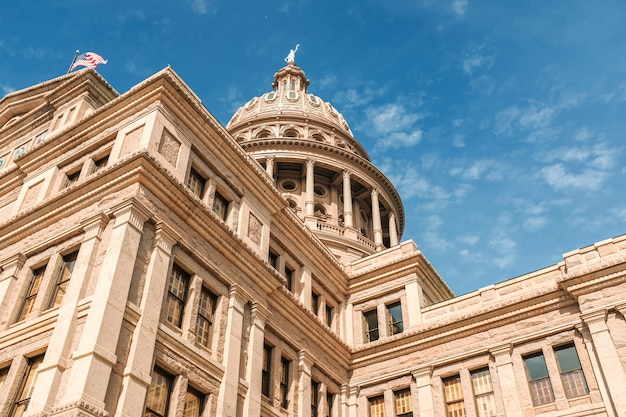 O ângulo baixo disparou da construção de texas capitol sob um céu azul bonito. cidade de austin, texas